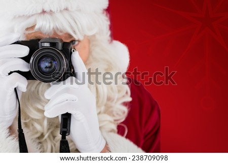 Portrait of santa taking a photo against red snowflake background