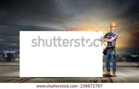Young repairman with white blank banner. Place for text