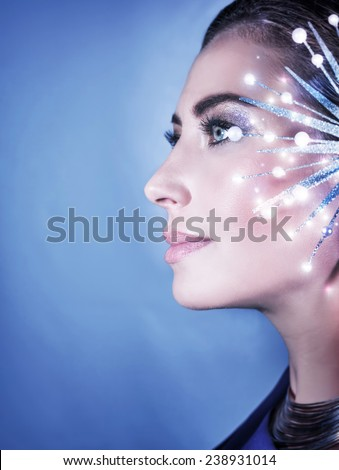 Side view of beautiful woman portrait on blue background, gorgeous female with shiny snowflake accessories, Fashion Christmas look #238931014
