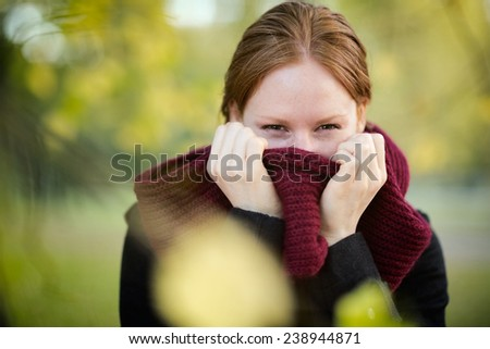 Closeup portrait of a young woman hiding behind a red scarf. Photographed in a city park in the Autumn or Fall. #238944871