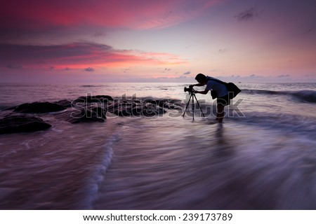 Silhouette of a photographer with dramatic waves at sunset in Sabah, Borneo, East Malaysia