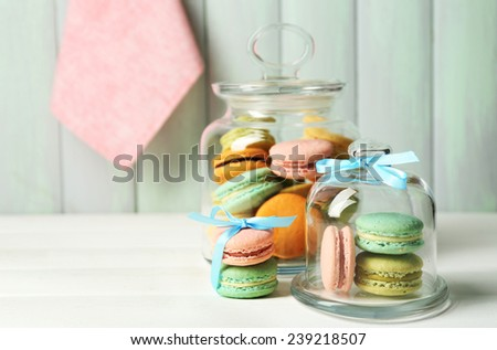 Gentle colorful macaroons in glass jars on color wooden table background #239218507