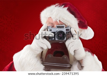 Santa is taking a picture against red background