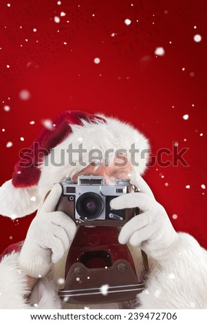 Santa is taking a picture against red snowflake background