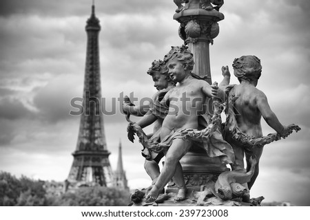 Scenic postcard view in Paris, France with statues of cherubs on a street lamp on the Pont Alexandre III Bridge with the Eiffel Tower standing in black and white monochrome