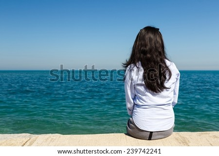 Young Asian woman sits at Lake Michigan in the Hyde Park area of Chicago, IL, USA on a sunny day. #239742241