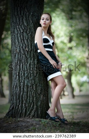 Beautiful brunette girl posing on the alley in the park #239762389