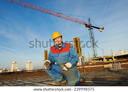 builder worker knitting metal rebars into framework reinforcement for concrete pouring at construction site #239998375
