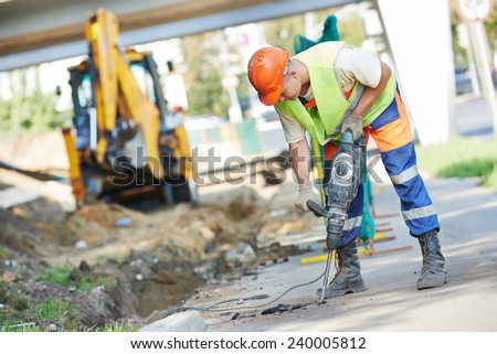 Builder worker with pneumatic hammer drill equipment breaking asphalt at road construction site Royalty-Free Stock Photo #240005812