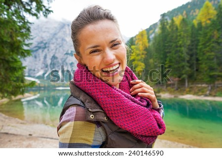 Portrait of happy young woman on lake braies in south tyrol, italy #240146590