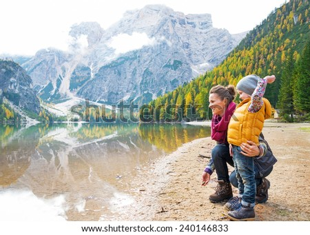 Mother and baby throwing stones on lake braies in south tyrol, italy #240146833