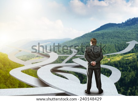 Businessman stands choosing his way Royalty-Free Stock Photo #240148429