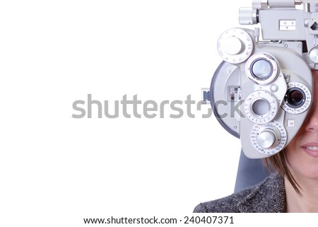 closeup of eyesight measurement to a young woman with a optical phoropter - copy space area on the left  Royalty-Free Stock Photo #240407371