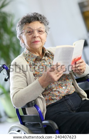 Disabled elderly woman in wheelchair reading book #240407623