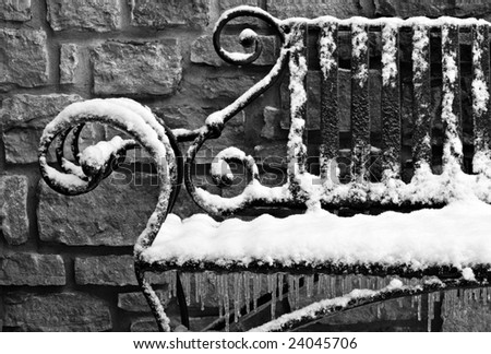 Black and white image of decorative wrought iron bench with snow and ice. Royalty-Free Stock Photo #24045706