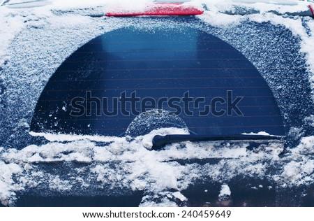 Winter frozen back car window, texture freezing ice glass background Royalty-Free Stock Photo #240459649