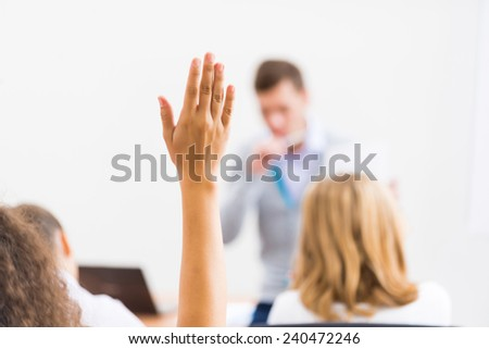 image of a female hand raised in university classroom Royalty-Free Stock Photo #240472246