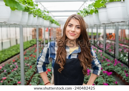 Florists woman working with flowers in a greenhouse. #240482425
