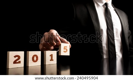 New Year Concept - Businessman Arranging Small Wooden Blocks with Date 2015 on a Pure Black Background. #240495904
