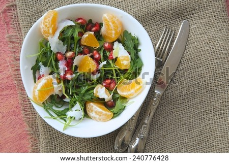 Fitness salad with tangerines,rucola leaves,pomegranate grains,olive oil, and parmesan cheese.Fork and a knife on a sackcloth. Top view #240776428