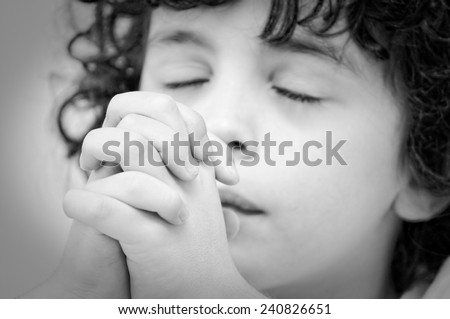 Young child praying  intensely and with reverence to God during his daily devotional, Christian boy relationship with Jesus. Black and white image #240826651