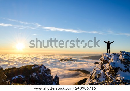 hiker celebrating success on top of a mountain in a majestic sunrise Royalty-Free Stock Photo #240905716