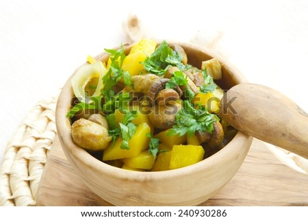 Light lunch- baked potatoes with mushrooms,onion,curcuma and fresh leaves of parsley in a olive wood dish. Mushrooms in the background. #240930286