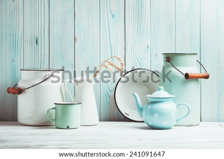 Enamelware on the kitchen table over blue wooden wall #241091647