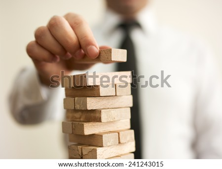 businessman builds a tower Royalty-Free Stock Photo #241243015