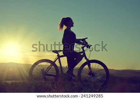 Girl on a bicycle in the sunset #241249285