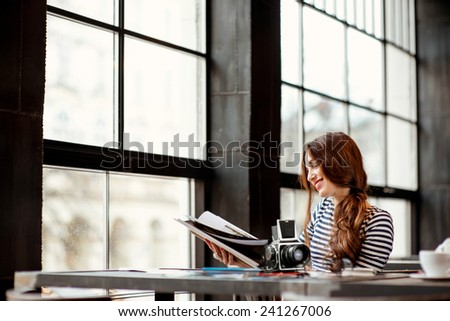 Young woman photographer watching photo album with old 6x6 frame camera and printed photos on the table sitting in the cafe with big windows