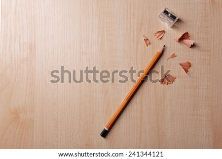 Pencil with sharpening shavings on wooden background