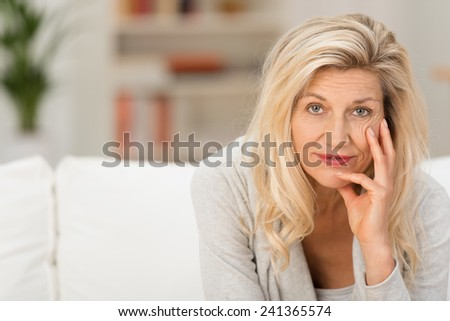 Thoughtful woman looking at the camera as she relaxes at home with her chin on her hand and a pensive expression #241365574