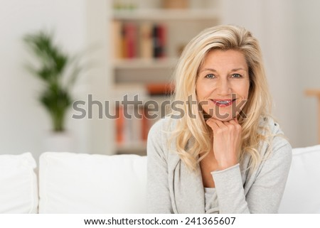 Close up Pretty Adult Woman Sitting on White Sofa with Hand on the Chin. Captured her While Looking at the Camera. #241365607