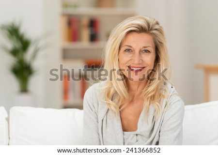 Attractive stylish middle-aged blond woman sitting on a sofa in her living room smiling at the camera, head and shoulders portrait #241366852