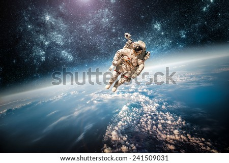 Astronaut in outer space against the backdrop of the planet earth. Elements of this image furnished by NASA. #241509031