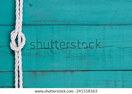 White rope with knot on blank  antique teal blue rustic wooden background Royalty-Free Stock Photo #241558363