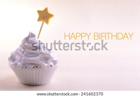 Delicious cupcake with star on stick and Happy Birthday text on light background