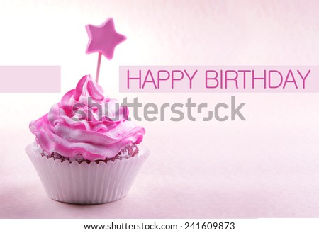 Delicious cupcake with star on stick and Happy Birthday text on light pink background