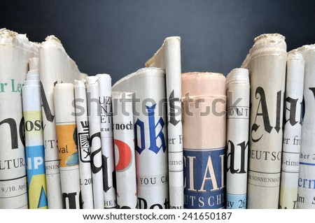 News - Folded newspapers in front of black wall Royalty-Free Stock Photo #241650187