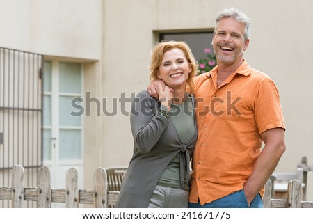 Portrait Of Happy Mature Couple Standing In Front Of House #241671775