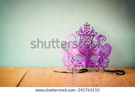 Mysterious Venetian masquerade mask on wooden table. retro filtered image