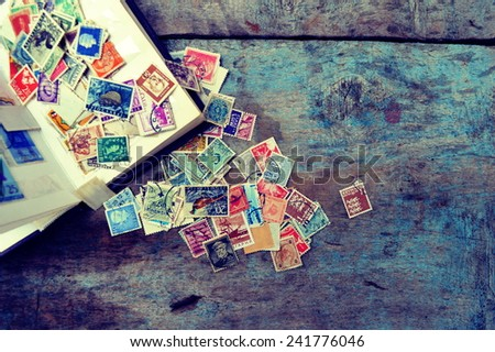 Old post stamps on a wooden background #241776046