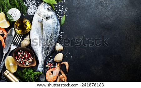 Delicious fresh fish on dark vintage background. Fish with aromatic herbs, spices and vegetables - healthy food, diet or cooking concept  Royalty-Free Stock Photo #241878163