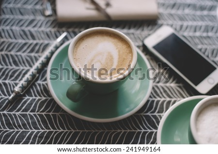 Fresh cup of cappuccino in a green cup with a saucer on a coffee table with a smartphone and a notebook #241949164