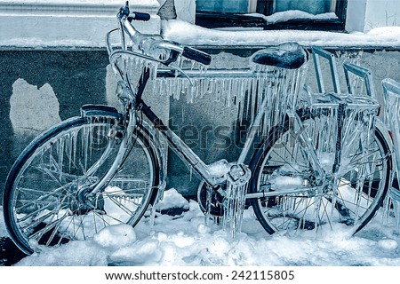 Blue look at ice icicles formed on a parked bicycle. Royalty-Free Stock Photo #242115805