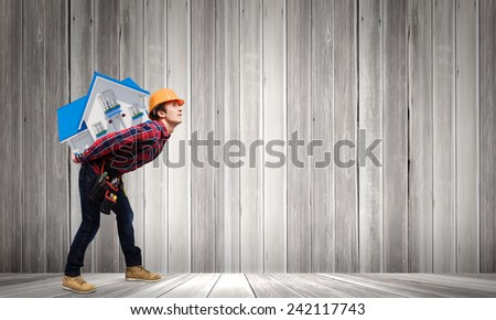 Young smiling craftsman carrying house model on back #242117743