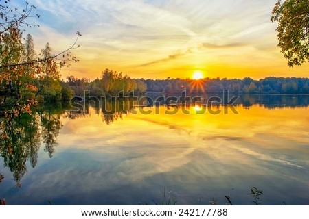 Autumn sunset on the lake with reflection of sun in water #242177788