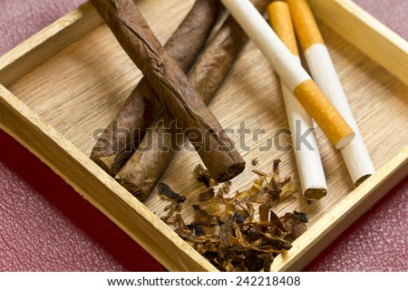 Tobacco, cigarettes, cigars, smoking, etc. on red leather background  Royalty-Free Stock Photo #242218408