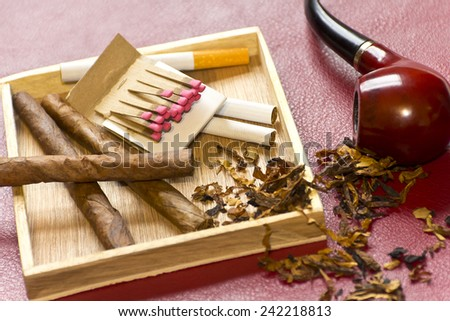 Pipe, tobacco, cigarettes, cigars, smoking, etc. on red leather background  Royalty-Free Stock Photo #242218813